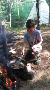 Kid cooking over an open fire